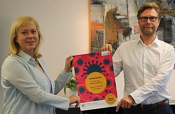 Annett Roswora und Dirk Adams halten Plakat der Impfkampagne