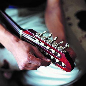 Person stimmt Gitarre