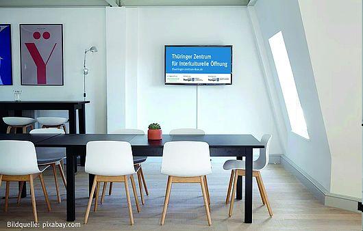 Bild eines Besprechungsraumes mit dem Logo des Zentrums für Interkulturelle Öffnung